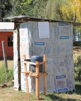 Finished Toilet with hand washing station. On this example, empty, clothe cement bags were used to demonstrate that any material can be utilized to cover the structure.